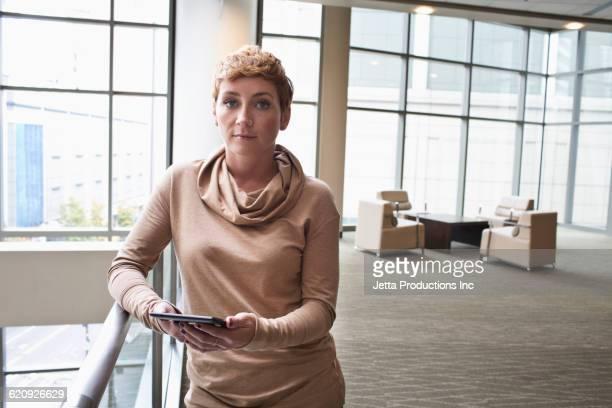 Caucasian businesswoman using digital tablet in office