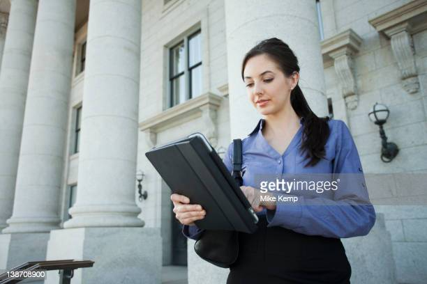 caucasian businesswoman using digital tablet outdoors - regierung stock-fotos und bilder