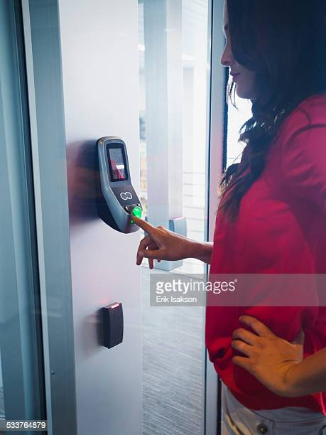 Caucasian businesswoman using fingerprint lock system in office