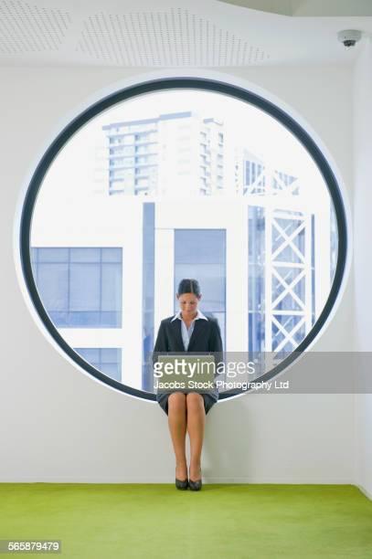 Caucasian businesswoman using laptop at office window