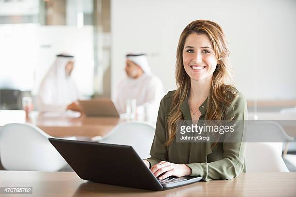 Caucasian Businesswoman using laptop in Middle East office