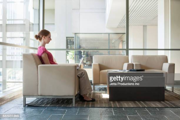 Caucasian businesswoman using laptop in office lobby