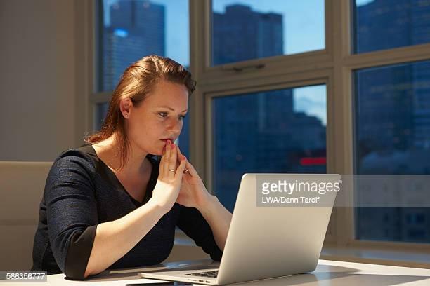 Caucasian businesswoman using laptop in office