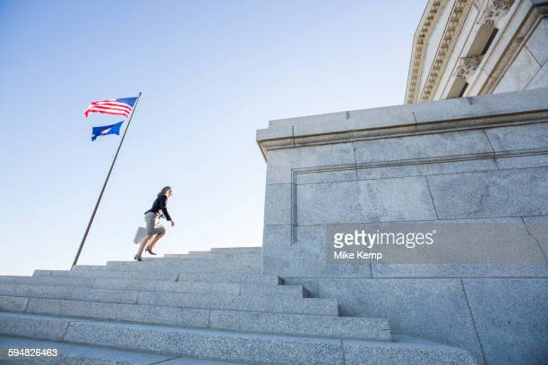 Caucasian businesswoman walking on courthouse steps