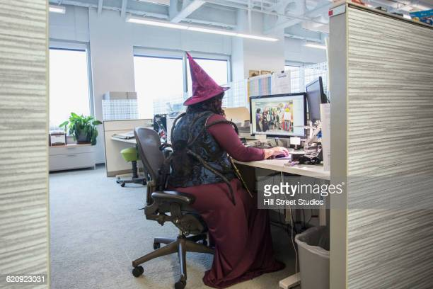 Caucasian businesswoman wearing witch costume in office