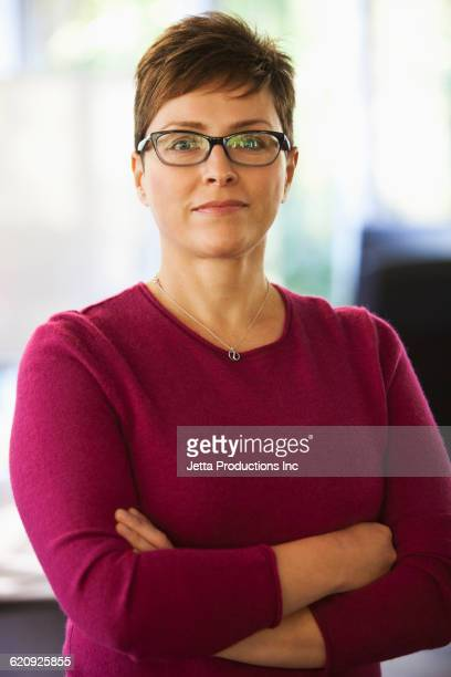 Caucasian businesswoman with arms crossed in office
