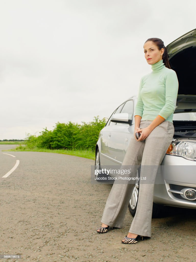 Caucasian businesswoman with broken down car on rural road : Stock Photo