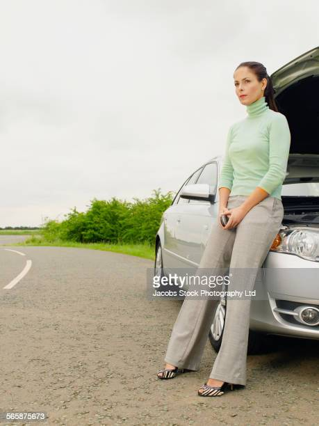 Caucasian businesswoman with broken down car on rural road