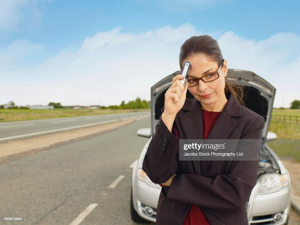 Caucasian businesswoman with broken-down car on rural road : Stock Photo