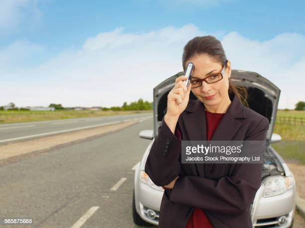Caucasian businesswoman with broken-down car on rural road