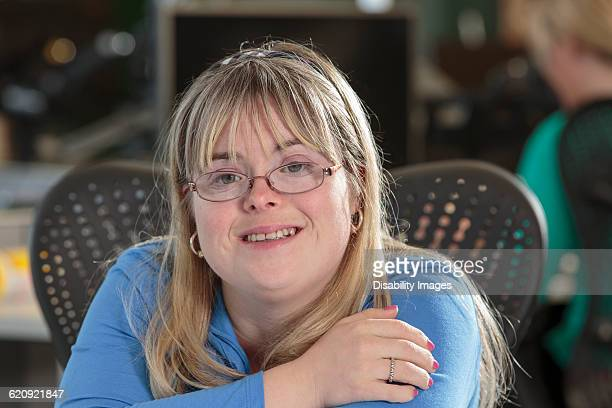 Caucasian businesswoman with Down Syndrome smiling in office