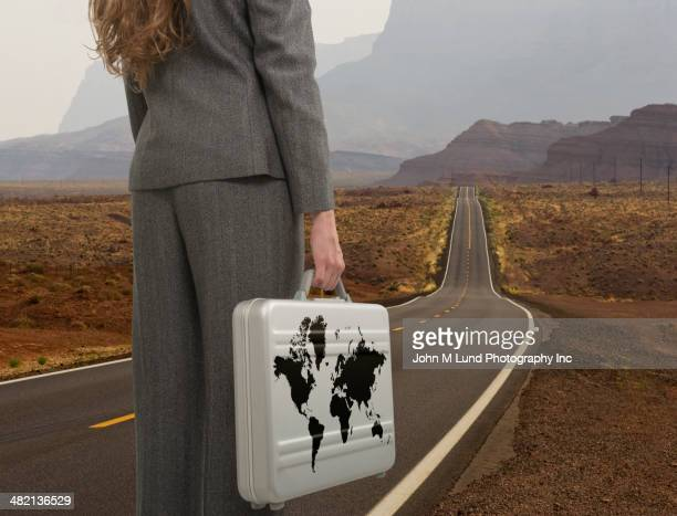 Caucasian businesswoman with world briefcase on open road