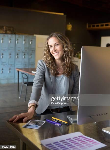 Caucasian businesswoman working at desk in office