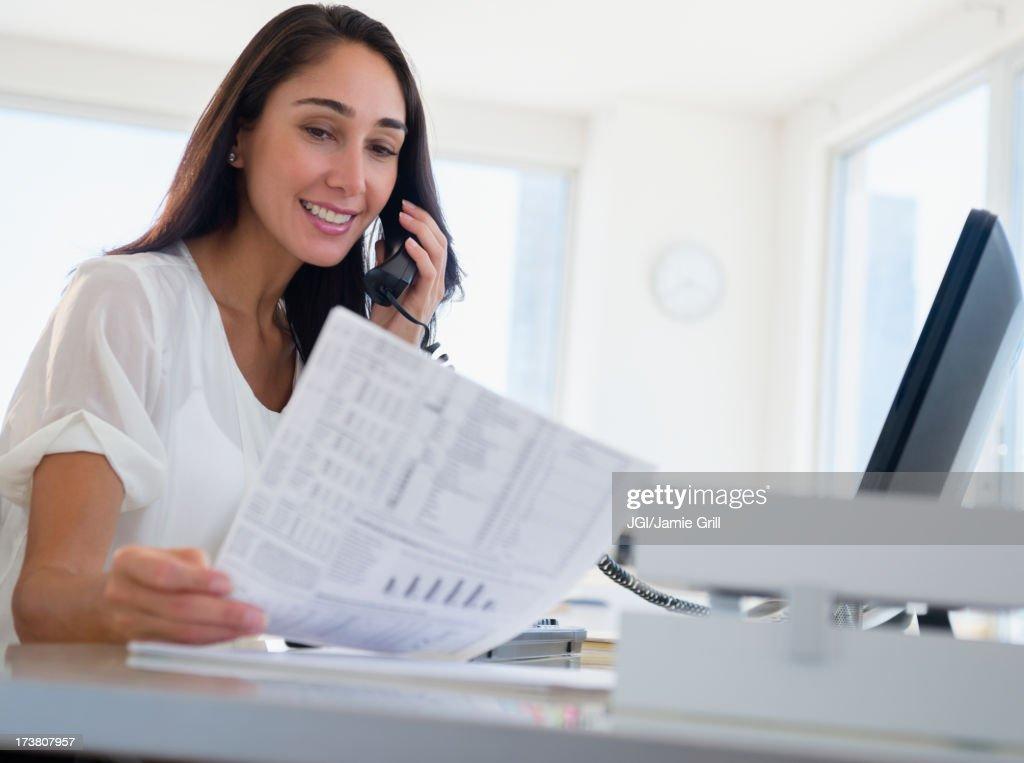 Caucasian businesswoman working at desk : Stock Photo