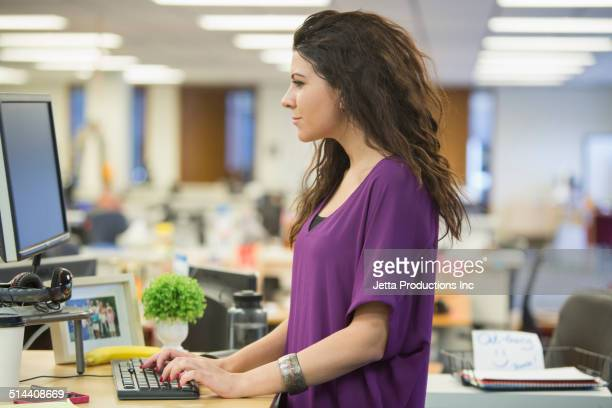 caucasian businesswoman working at desk - stand stock photos and pictures