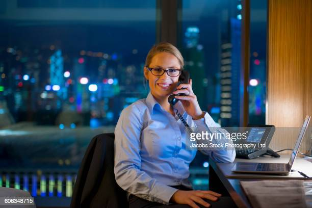 Caucasian businesswoman working late in office