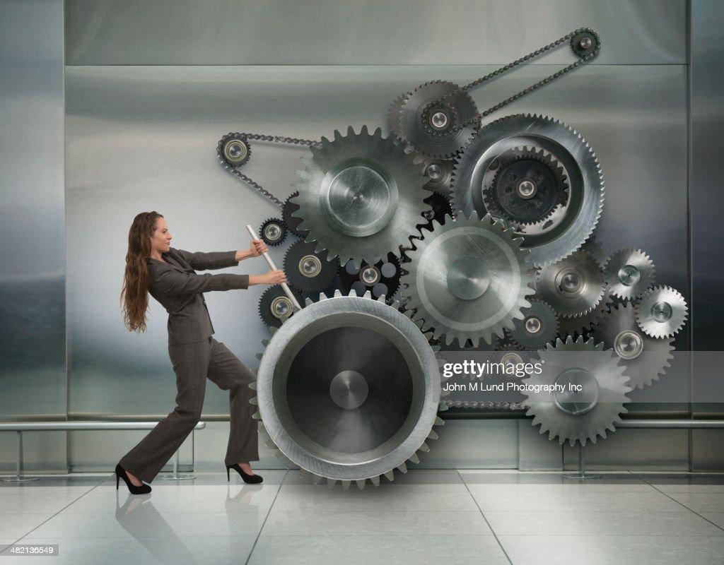 Caucasian businesswoman working metal cogs : Stock Photo