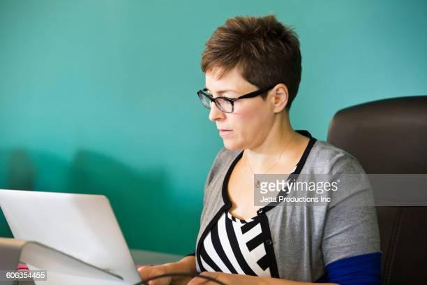 Caucasian businesswoman working on laptop