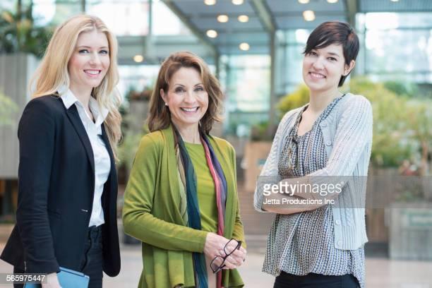 Caucasian businesswomen smiling in office lobby