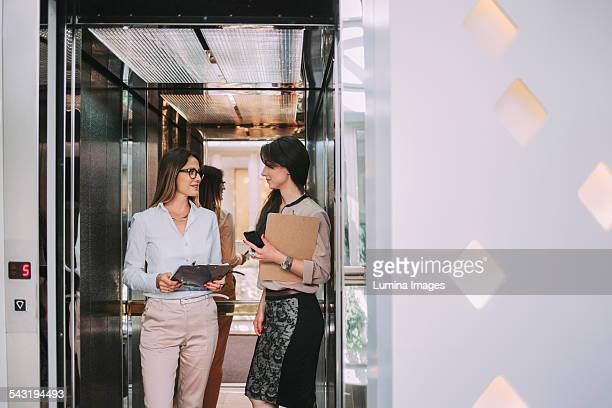 Caucasian businesswomen talking in elevator