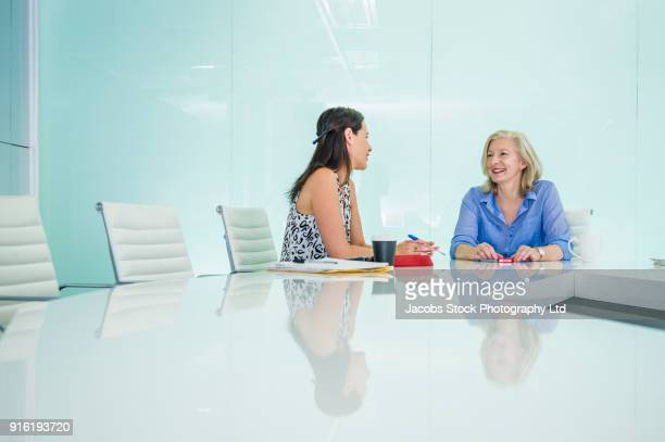 Caucasian businesswomen talking in modern conference room