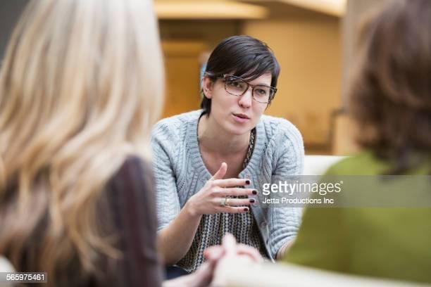 Caucasian businesswomen talking in office lobby