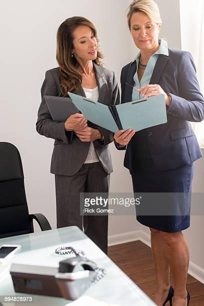 Caucasian businesswomen talking in office