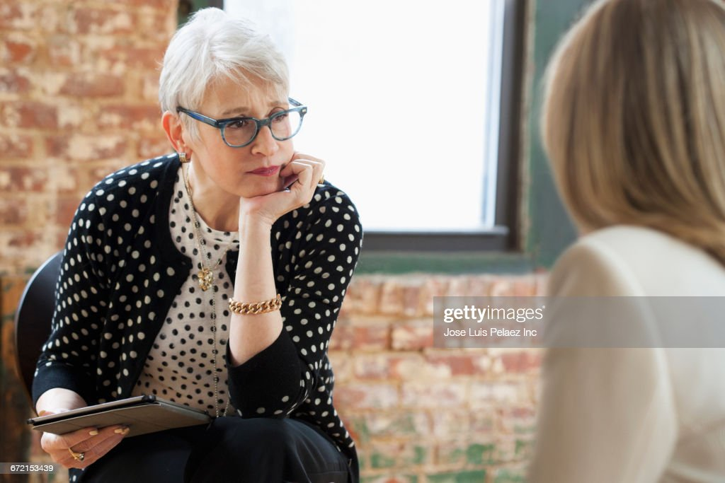 Caucasian businesswomen talking in office with digital tablet : Stock Photo
