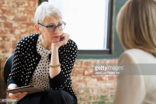 Caucasian businesswomen talking in office with digital tablet