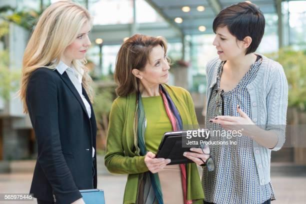 Caucasian businesswomen using digital tablet in office lobby