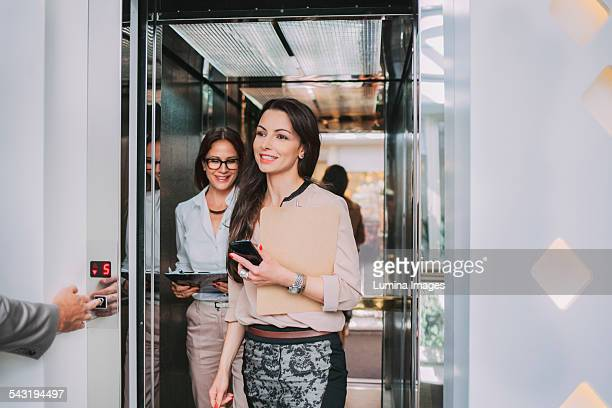 Caucasian businesswomen walking out of elevator