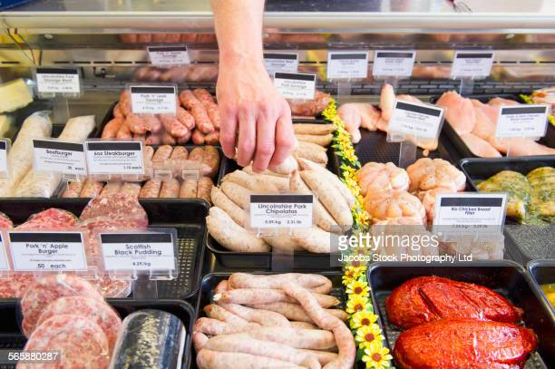 caucasian butcher selecting sausage from cooler in shop - lincolnshire stock pictures, royalty-free photos & images