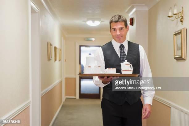 Caucasian butler carrying tea in hotel hallway