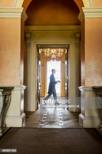 Caucasian butler carrying tray in mansion hallway