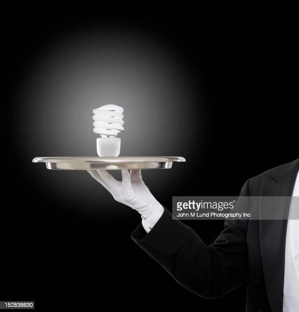 Caucasian butler holding CFL light bulb on tray