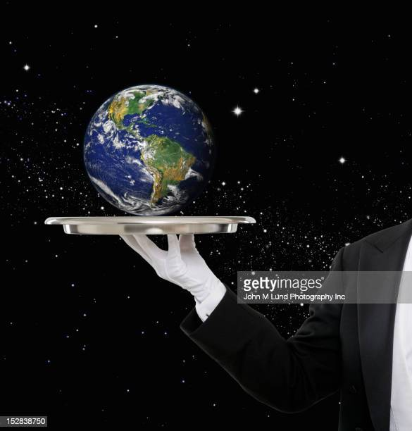 Caucasian butler holding Earth on tray