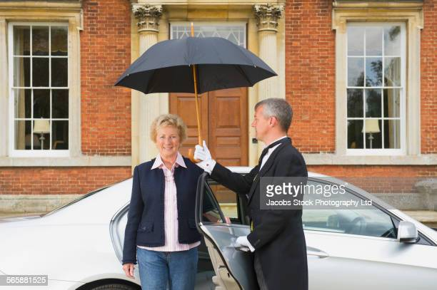 Caucasian butler holding umbrella outside car door for woman