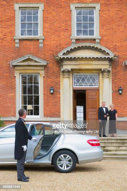 caucasian butler opening car door for couple outside mansion - travelstock44 stock pictures, royalty-free photos & images