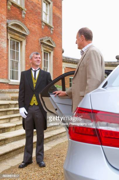 Caucasian butler opening car door for man