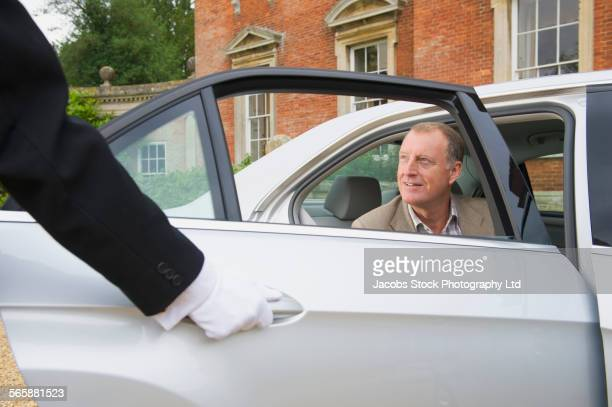 caucasian butler opening car door for man - travelstock44 stock pictures, royalty-free photos & images