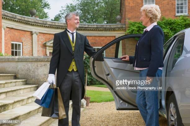 Caucasian butler opening car door for woman
