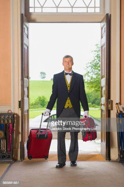 Caucasian butler rolling luggage in mansion front door