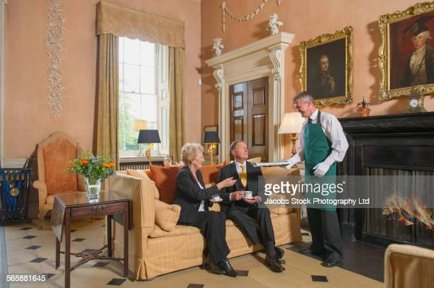 Caucasian butler serving business people in formal mansion parlor