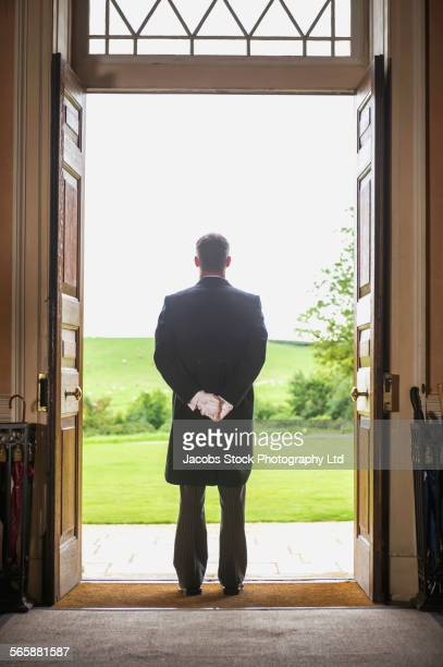 Caucasian butler standing at mansion front door