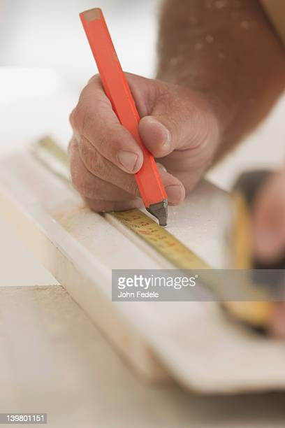 Caucasian carpenter measuring lumber