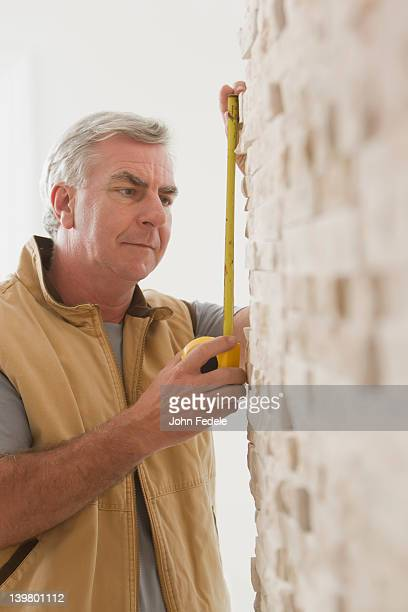 Caucasian carpenter measuring wall