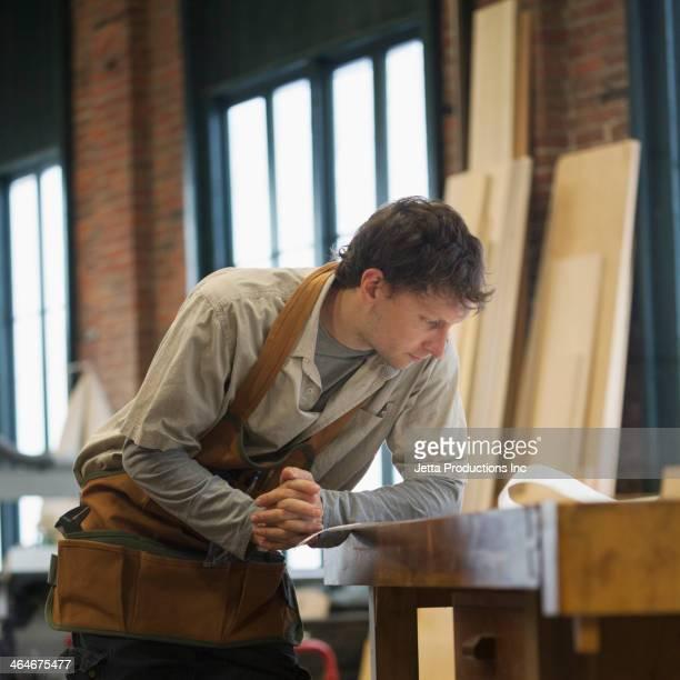 Caucasian carpenter reviewing blueprint in workshop