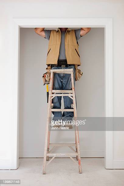 caucasian carpenter standing on ladder in doorway - low section stock pictures, royalty-free photos & images