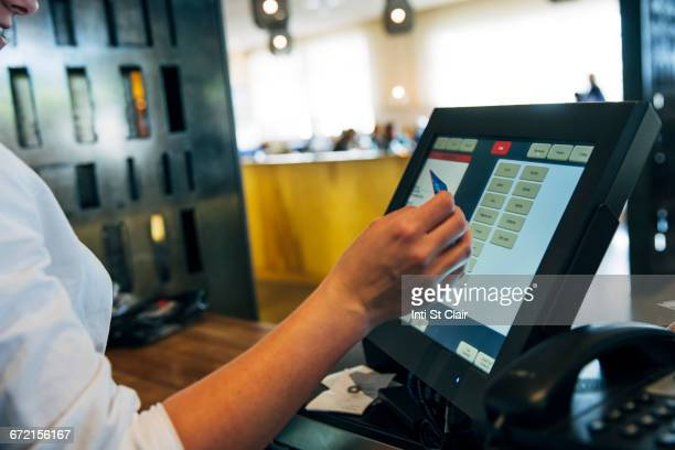 Caucasian cashier using touch screen to process credit card payment
