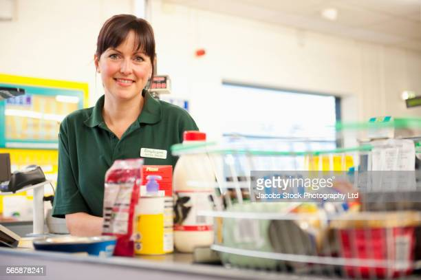 caucasian cashier working at grocery store checkout - weibliche person stock-fotos und bilder